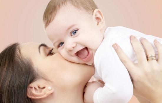 엄마에게 안겨 웃고 있는 아기